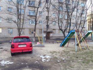 Парковка автомобиля во дворе рядом с детскими площадками